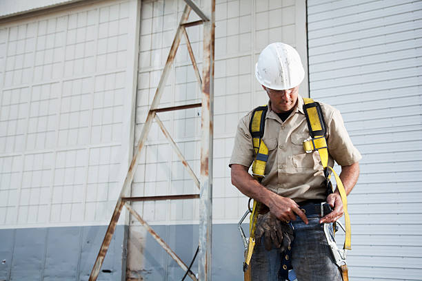 Worker putting on safety harness Worker (30s) with work gloves, hard hat, safety glasses, putting on harness. safety harness stock pictures, royalty-free photos & images