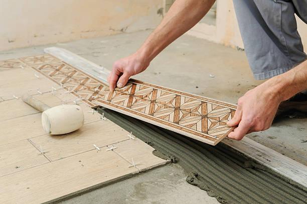 worker putting tiles on the floor. - keramik fliesen handwerk stock-fotos und bilder