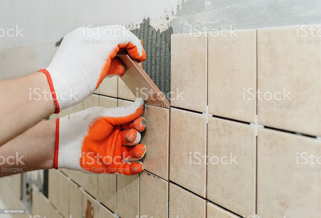 Worker  putting  tiles on the wall in the kitchen. stock photo