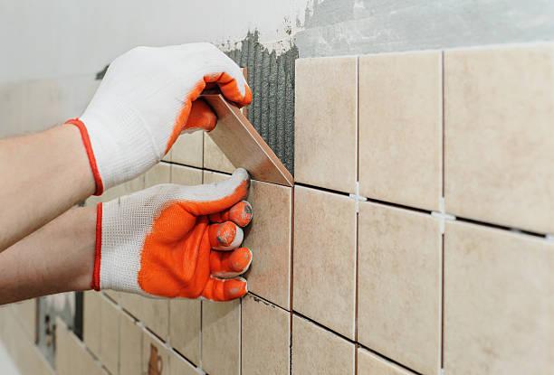 worker  putting  tiles on the wall in the kitchen. - fliesenkleber stock-fotos und bilder