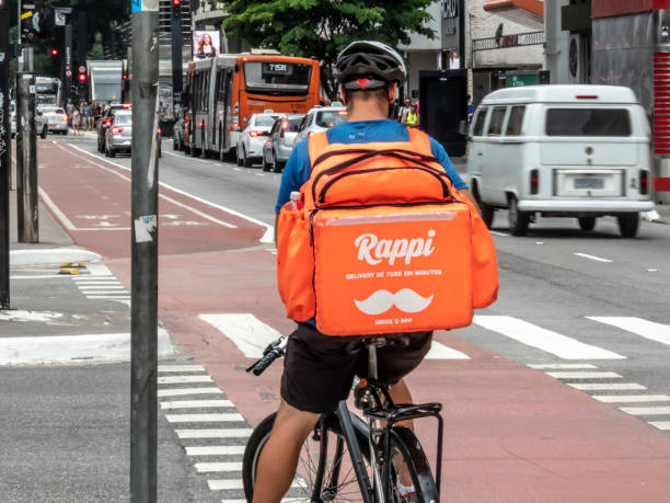 arbeiter rappi app auf dem fahrrad beliefert kunden in sao paulo stadt essen. - kinder die schnell arbeiten stock-fotos und bilder