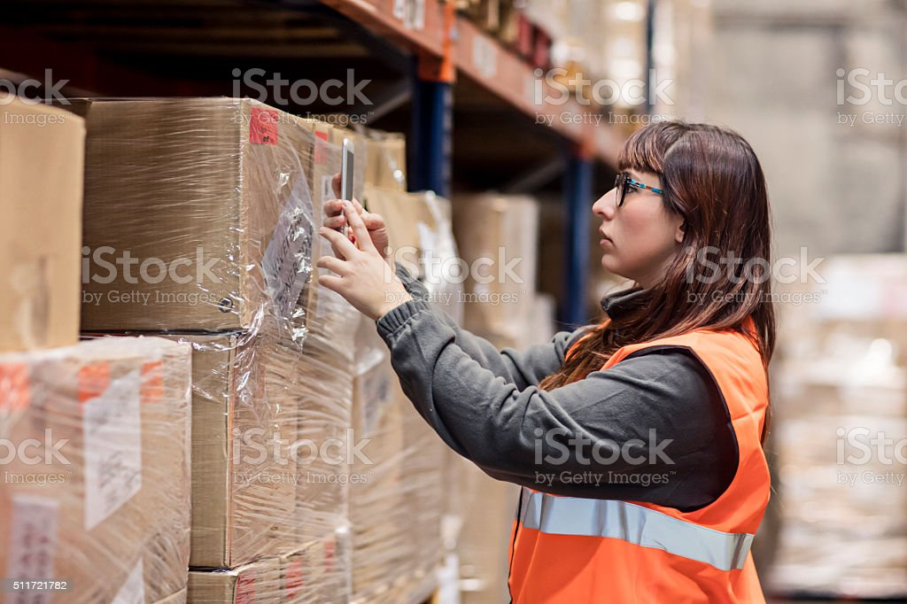 Worker reading the barcode with the mobile phone app stock photo