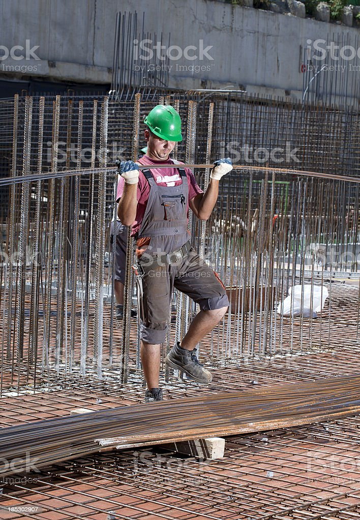 worker, rebar on construction site  positions, secures steel reinforcing bar stock photo