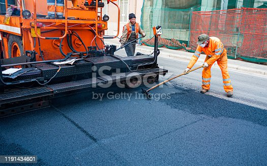 Worker regulate tracked paver laying asphalt heated to temperatures above 160 grades Celsius pavement on a runway