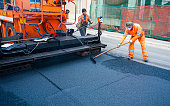 istock Worker regulate tracked paver laying asphalt heated to temperatures above 160 grades Celsius pavement on a runway 1191434601