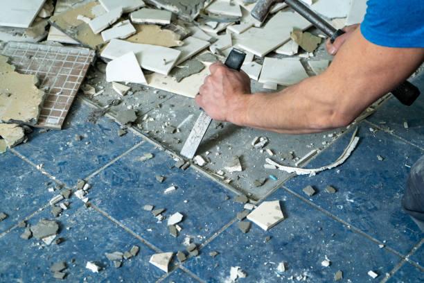 Arbeiter zu entfernen, alte Fliesen in einem Badezimmer mit Hammer und Meißel zu zerstören – Foto