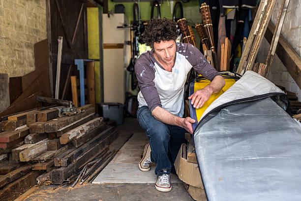 worker removing surfboard from cover in workshop - surf garage bildbanksfoton och bilder