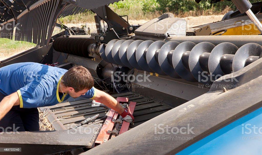 Worker repair harvester on field. stock photo