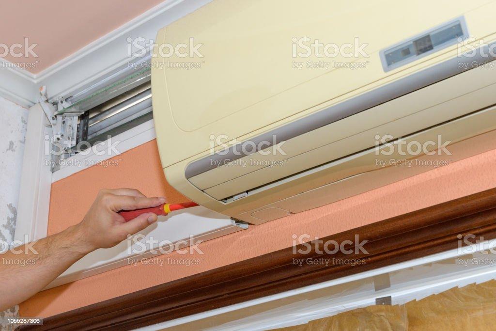 worker repairing air conditioner stock photo