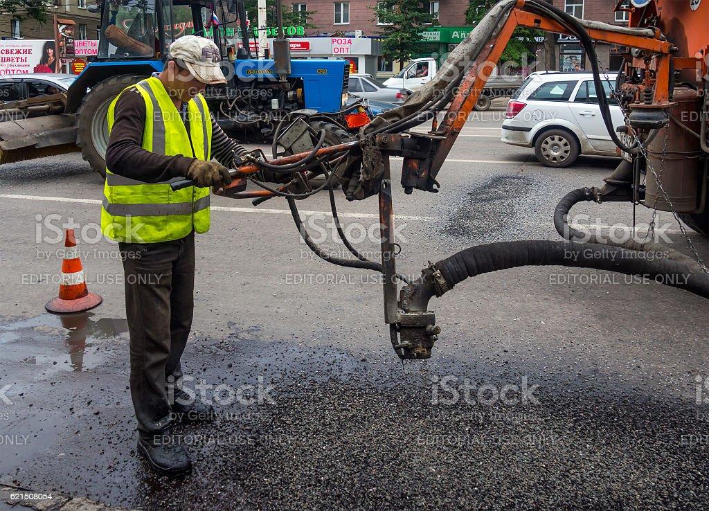 Worker repairing hole in the asphalt on a city street photo libre de droits