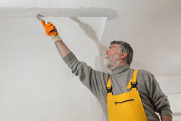 Arbeiter reparieren Stuckarbeiten an der Decke – Foto