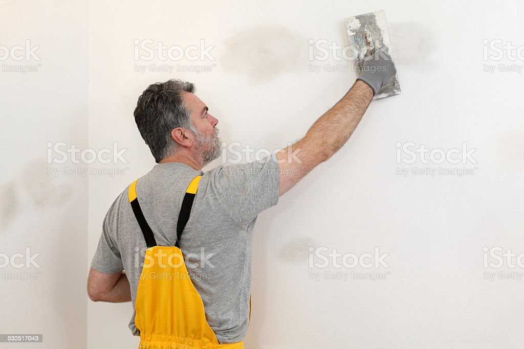 Worker repairing plaster at wall stock photo