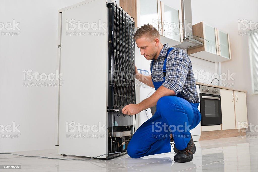 Trabajador reparar refrigerador en casa foto de stock libre de derechos