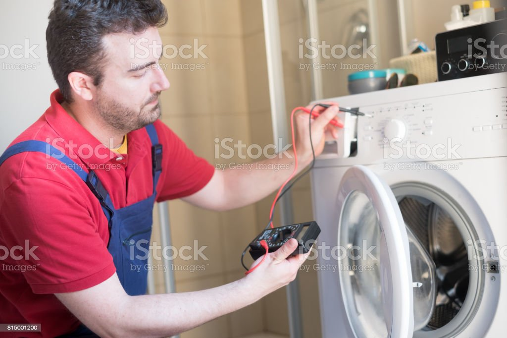 Worker repairing the washing machine in the bathroom stock photo