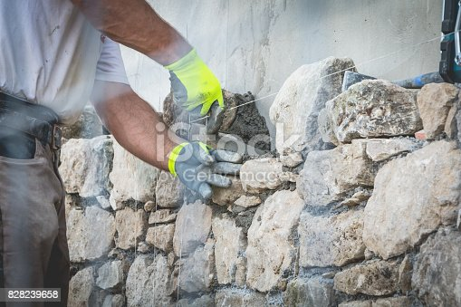 worker rides a stone wall on a traditional renovation site of NOIRMOUTIER, FRANCE