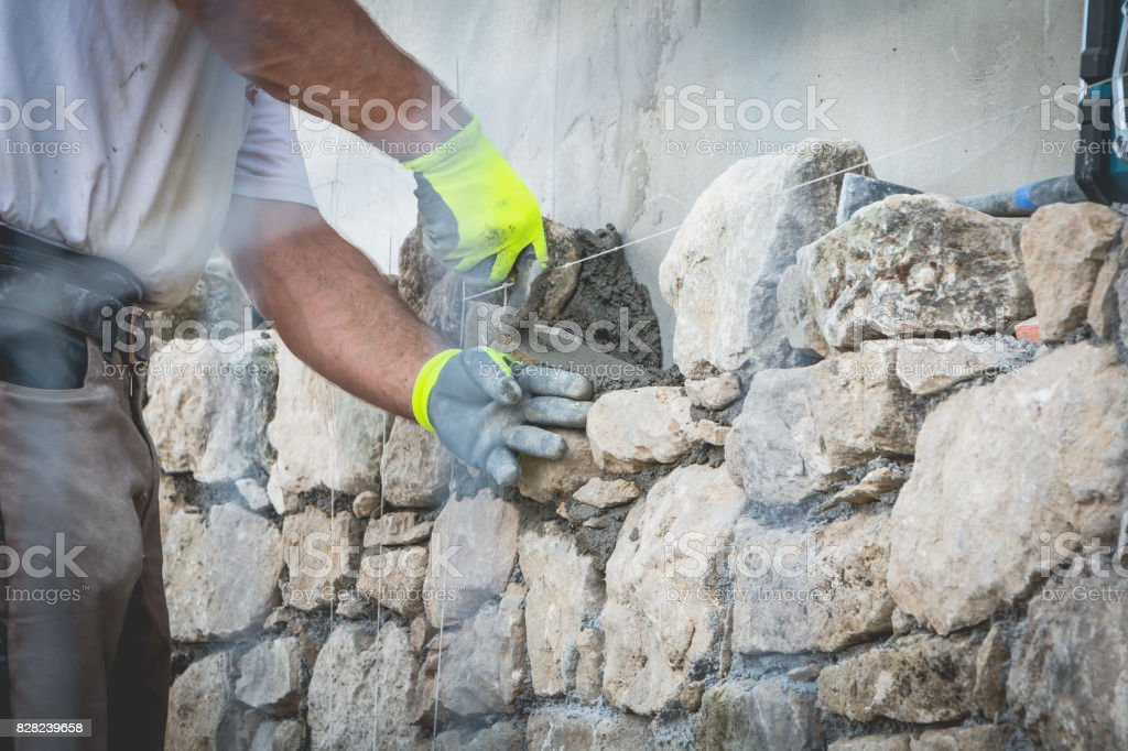 worker rides a stone wall on a traditional renovation site stock photo