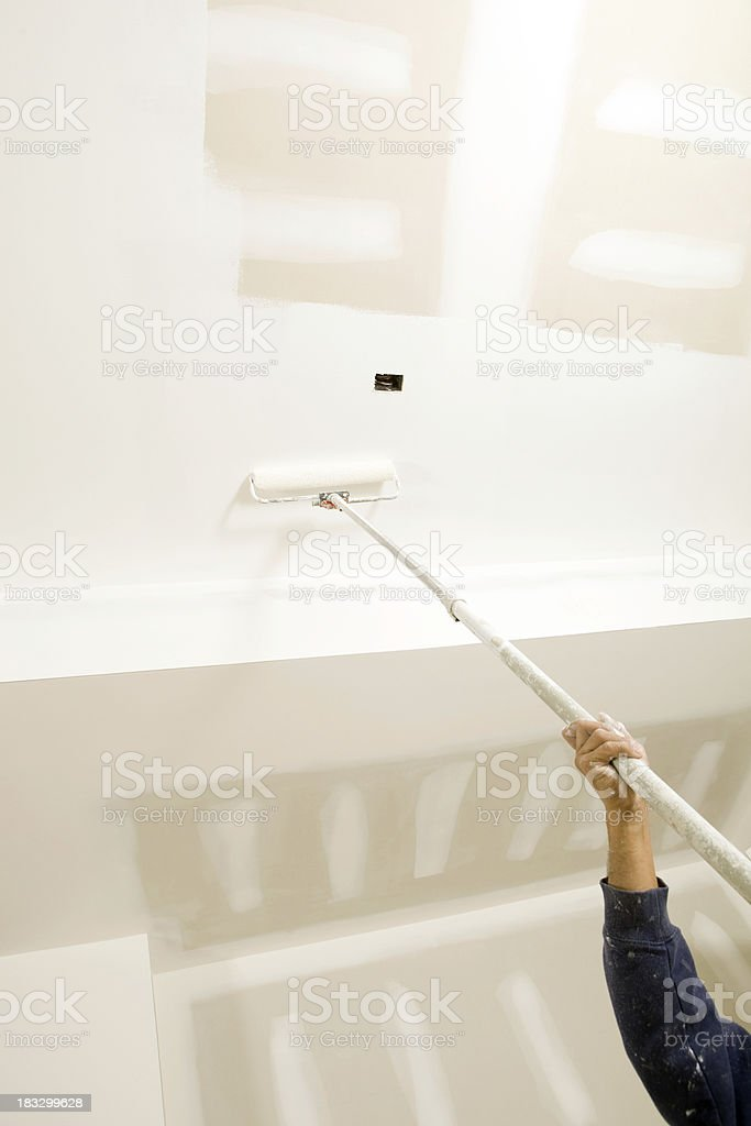 Worker Roller Painting a New Garage Ceiling stock photo