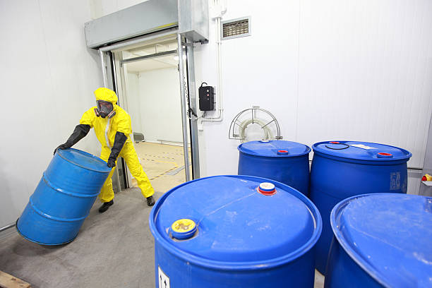 Worker rolling the barrel with toxic substance stock photo