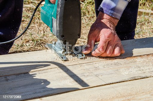 worker sawing boards with a jigsaw at a construction site and sawdust fly