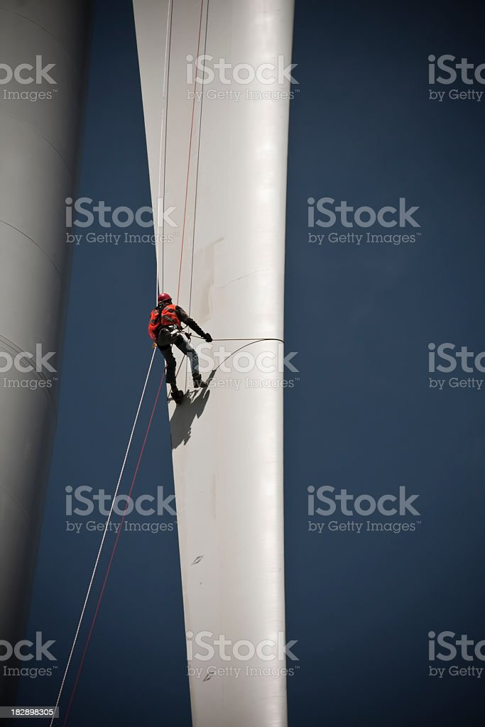 A worker scaling a tall structure stock photo
