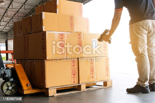 Worker scanning barcode scanner on package boxes on pallet, warehouse industry delivery to transport