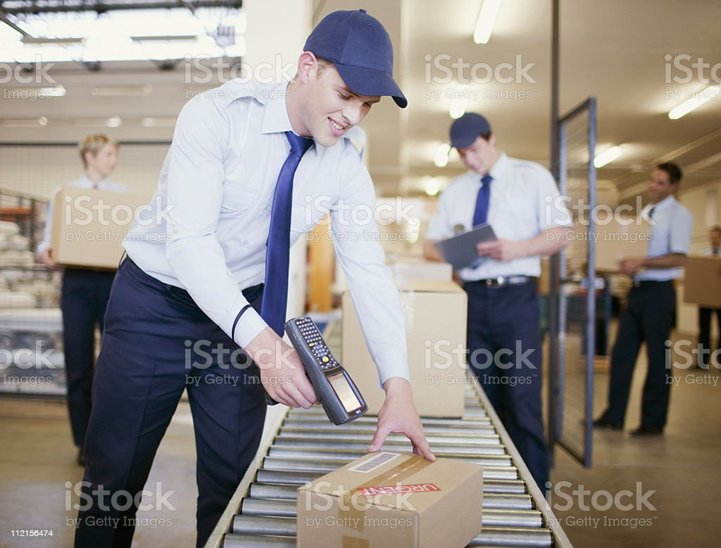 Worker scanning box on conveyor belt in shipping area foto