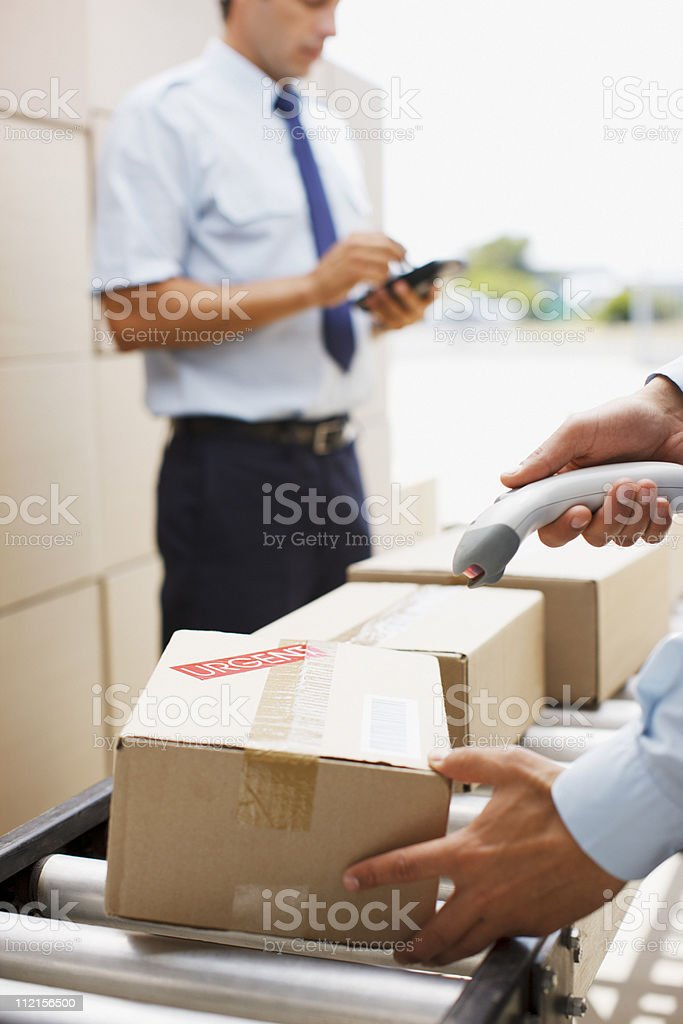 Worker scanning box on conveyor belt in shipping area royalty-free stock photo