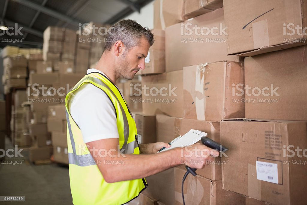 Worker scanning package in warehouse Side view of manual worker scanning package in the warehouse 30-39 Years Stock Photo