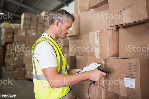 Worker Scanning Package In Warehouse Stock Photo - Download Image Now