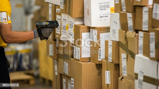 Male worker scanning barcode at warehouse.