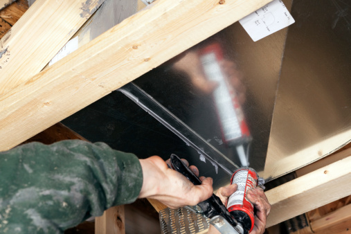 HVAC Worker Sealing House Air Duct Joint with Caulk