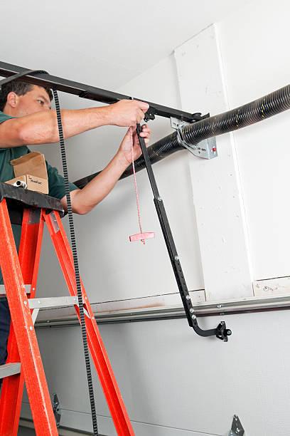 operaio di manutenzione dispositivi di apertura porte garage - molla foto e immagini stock