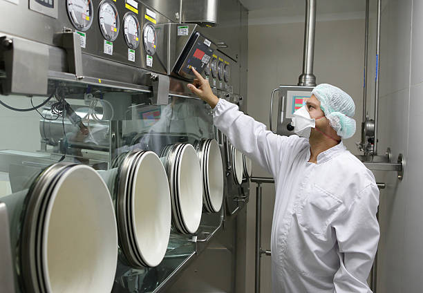 Worker set big glove box machine in pharmaceutical factory stock photo