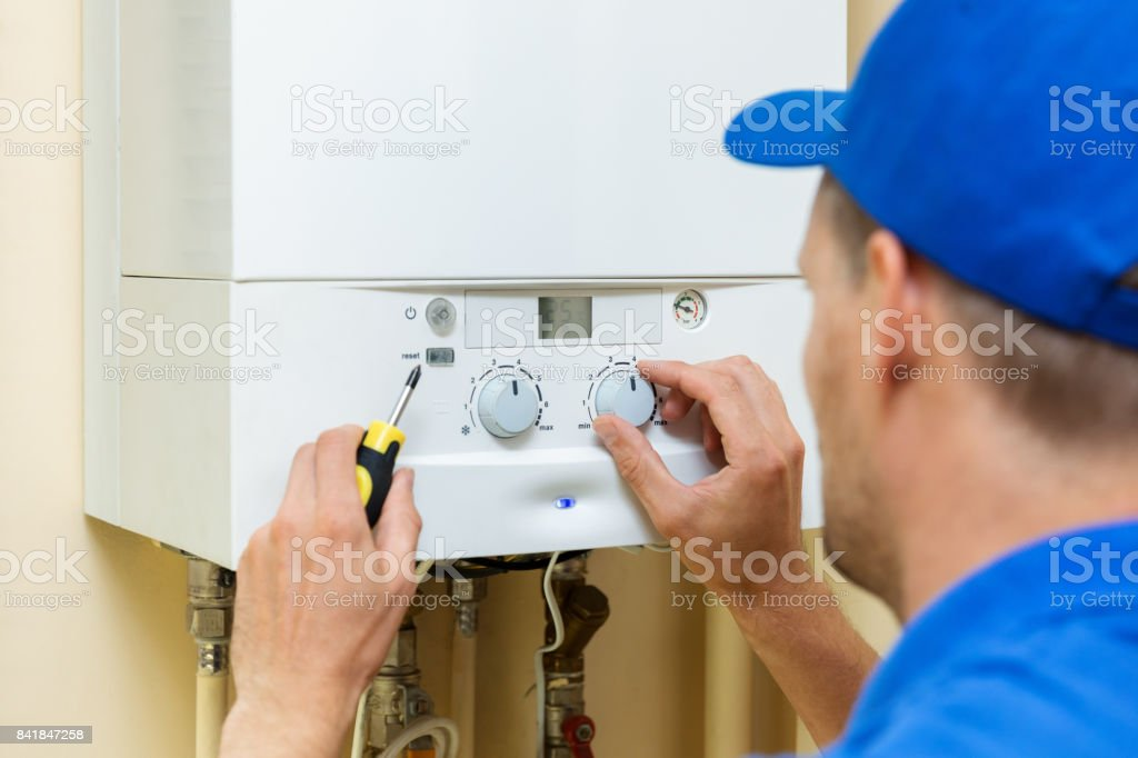 worker set up central gas heating boiler at home stock photo