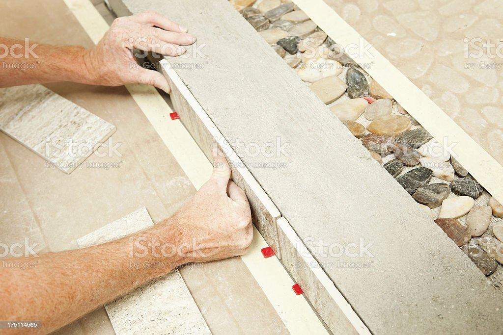 Worker Setting Shower Floor Tile stock photo