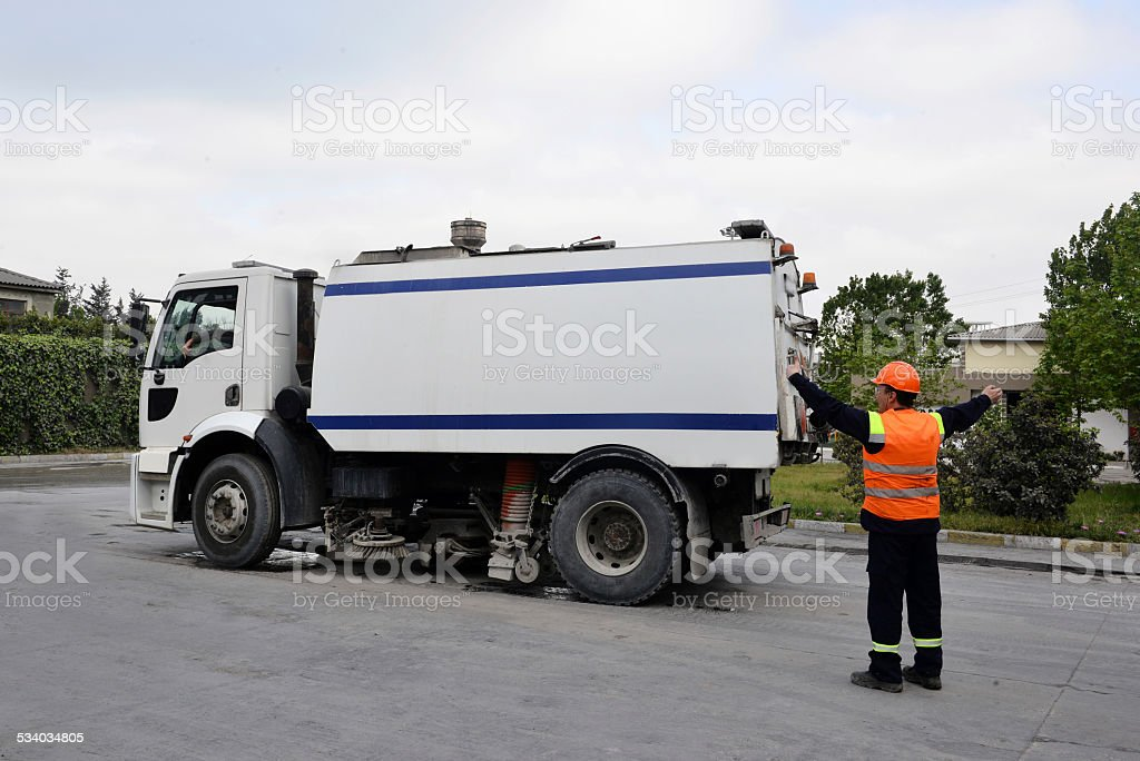 Worker showing parking spot to sweeping truck stock photo