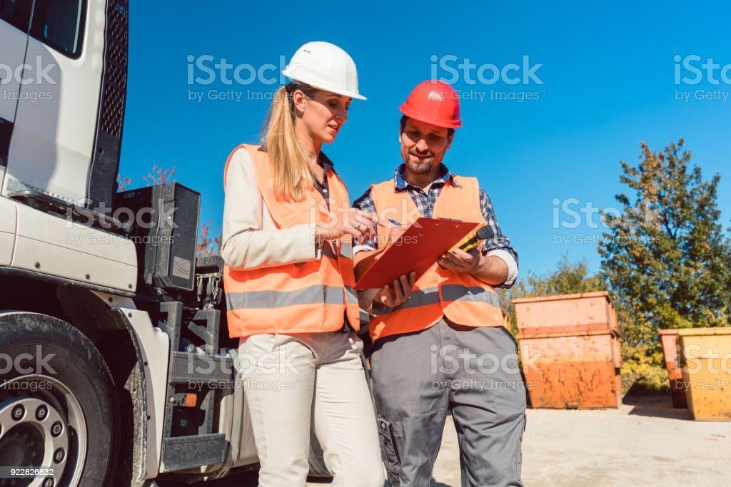 Worker signing papers to have delivered demolition rubble container stock photo