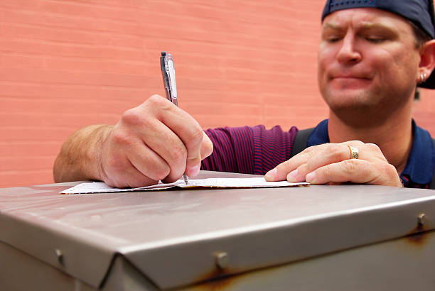 worker signing receipt - mikefahl stock pictures, royalty-free photos & images