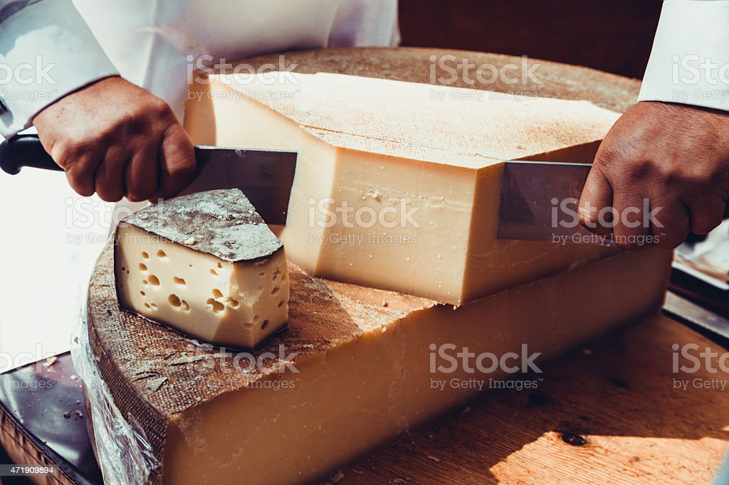 Worker slicing the cheese. stock photo