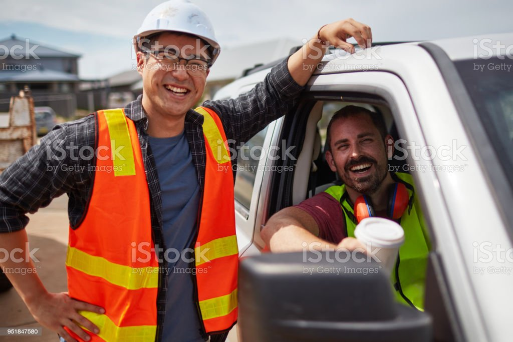Worker smiling by colleague sitting in car at site stock photo
