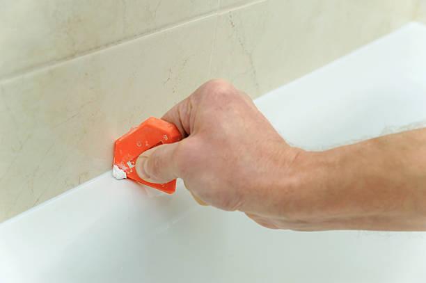 worker smoothing silicone sealant. - fugen reinigen stock-fotos und bilder