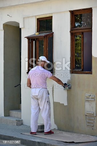 Sremski Karlovci, Serbia, 21st April 2018. - Worker smoothing texture of the external wall on the house