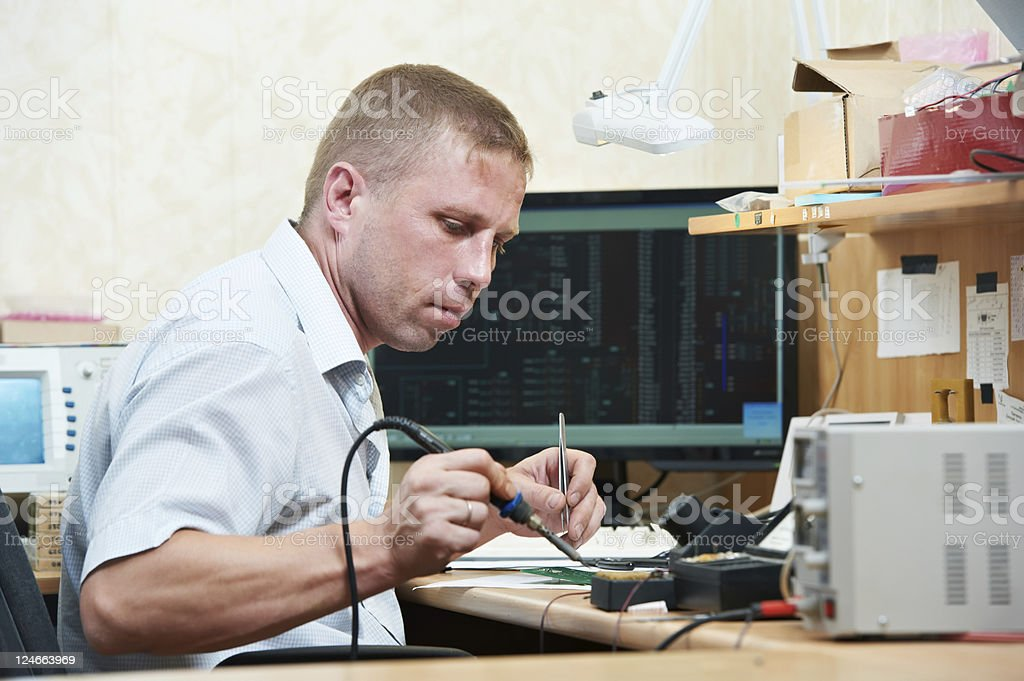 worker soldering microchip scheme royalty-free stock photo