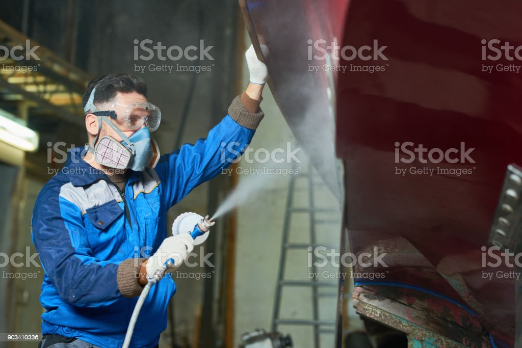 Worker Spray Painting Boats in Workshop stock photo