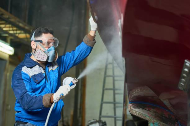 arbeiter spray malerei boote in werkstatt - legere arbeitskleidung stock-fotos und bilder