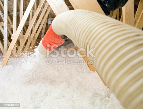 "A worker is spraying blown fiberglass insulation between attic trusses at a residential construction site. The completed application will be 22"" deep providing an insulation value of R-60."