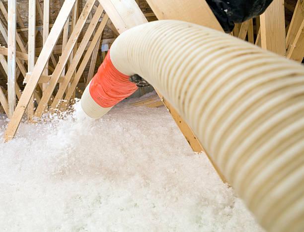Worker Spraying Blown Fiberglass Insulation between Attic Trusses stock photo
