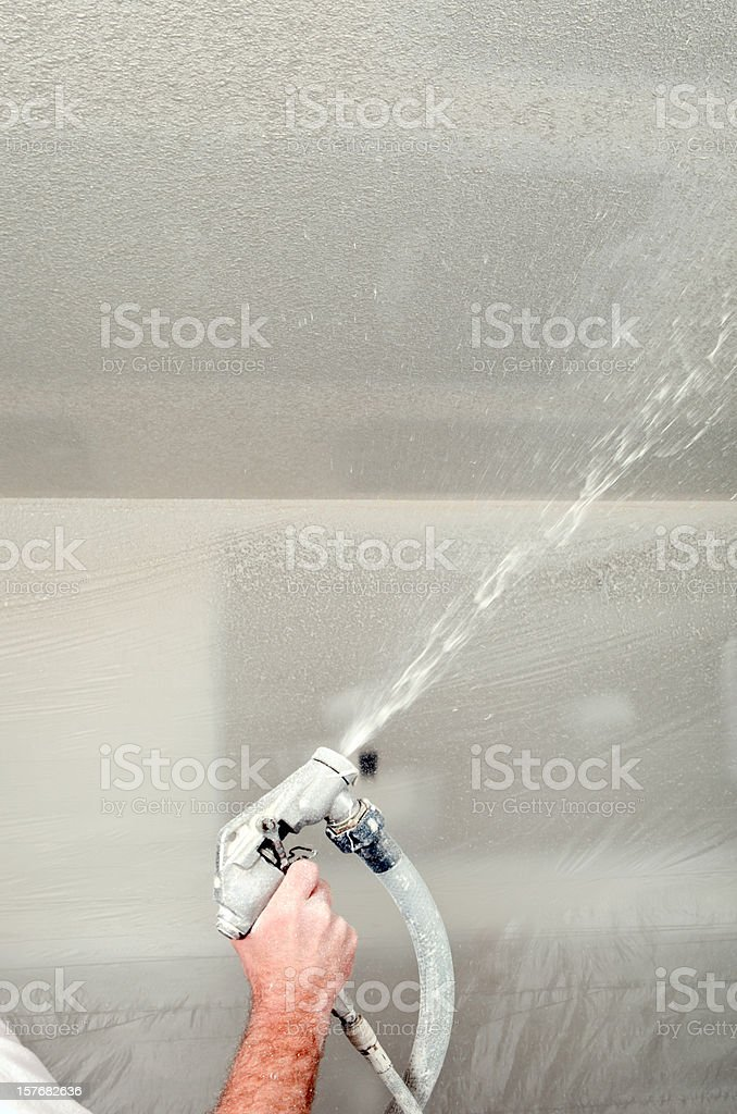 Worker Spraying Drywall Mud on a Ceiling for Knockdown Texture royalty-free stock photo