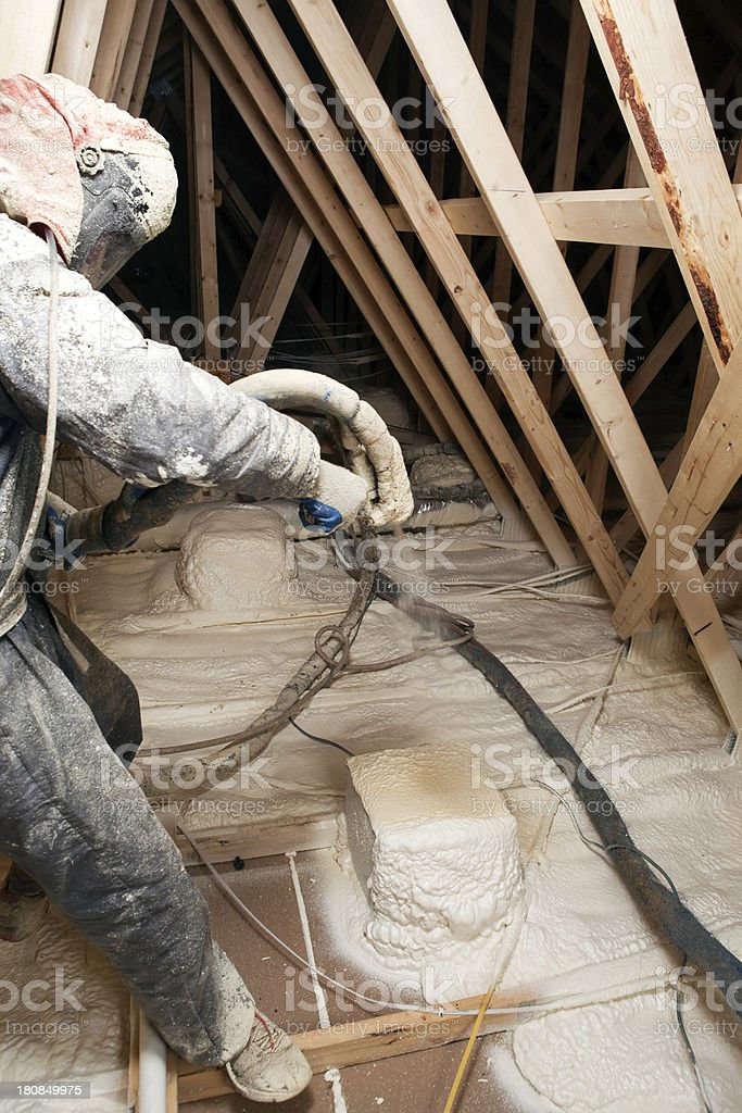 Worker Spraying Expandable Foam Insulation in House Attic stock photo