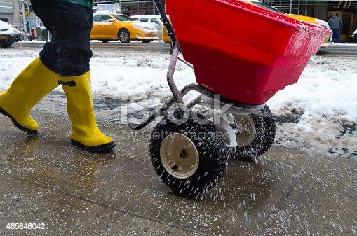 worker pushing salt spreader on icy New York City sidewalk during snow storm in winter.